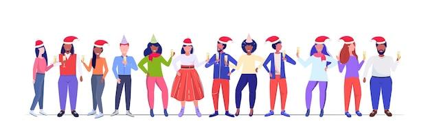 Mezclar personas de raza con sombreros de santa claus sosteniendo copas de champán feliz navidad feliz año nuevo vacaciones de invierno celebración de fiestas corporativas