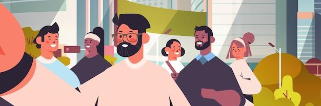 Mezclar personas de raza tomando selfie en la cámara del teléfono inteligente hombres felices mujeres caminando al aire libre haciendo auto foto paisaje urbano de fondo retrato horizontal ilustración vectorial