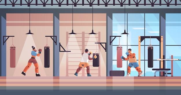 Mezclar raza boxeadores haciendo ejercicios con saco de boxeo entrenamiento estilo de vida saludable concepto de boxeo moderno club de lucha interior