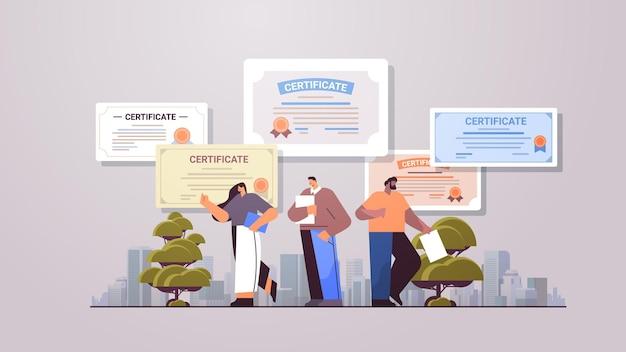Mezclar la raza empresarios graduados titulares de certificados graduados felices celebrando el título de diploma académico concepto de educación corporativa de longitud completa horizontal
