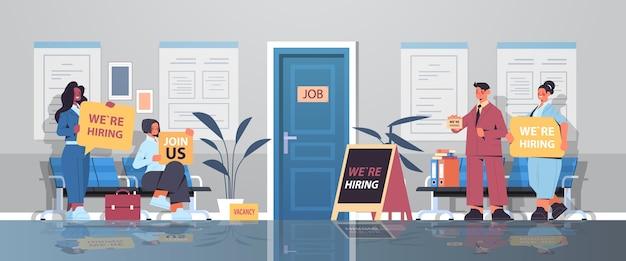 Mezclar la raza gerentes de recursos humanos que sostienen que estamos contratando únete a nosotros carteles vacante reclutamiento abierto concepto de recursos humanos oficina pasillo interior horizontal ilustración vectorial de longitud completa
