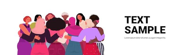 Mezclar la raza de las niñas abrazando de pie juntos el movimiento de empoderamiento femenino concepto de poder de las mujeres espacio de copia vertical