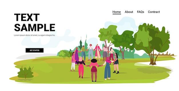 Mezclar la raza niñas tomados de la mano de pie juntos movimiento de empoderamiento femenino concepto de poder de las mujeres parque urbano paisaje espacio copia de fondo
