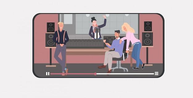 Mezclar raza personas que realizan en el estudio de grabación hombres mujeres transmisión en vivo concepto de transmisión de comunicación teléfono inteligente de pantalla completa aplicación móvil reproductor de video en línea horizontal