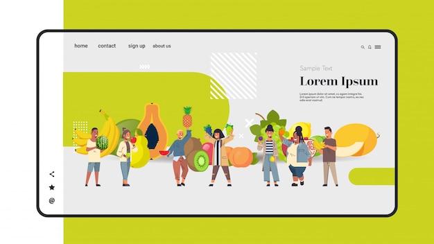Mezclar raza personas sosteniendo diferentes frutas tropicales saludable estilo de vida ecológico comida vegana concepto hombres mujeres grupo de pie juntos longitud completa copia espacio horizontal