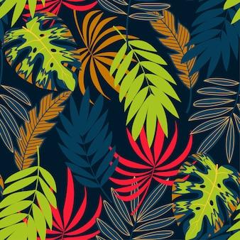 Modelo inconsútil tropical con plantas y hojas sobre un fondo oscuro