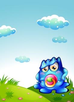 Un monstruo azul bebé en la cima de la colina