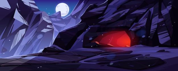Montañas con entrada a la cueva iluminadas desde adentro por la noche.