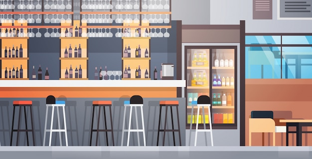 Mostrador de cafetería interior con botellas de alcohol y vasos en el estante
