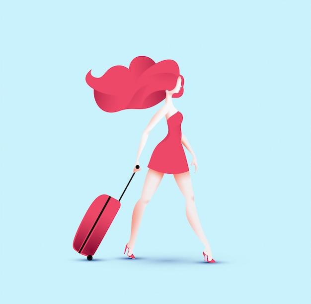 Muchacha bonita del viajero del pelirrojo en vestido rojo que camina con el bolso rojo del rodillo del viaje