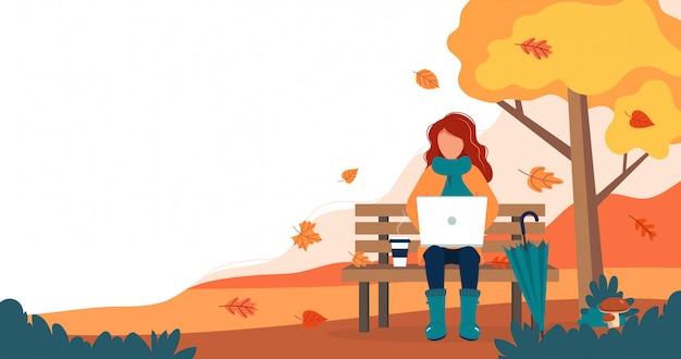 Muchacha con la computadora portátil que se sienta en banco en otoño.