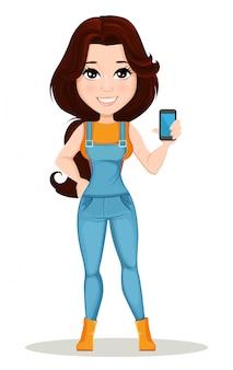 La muchacha del granjero vestida en mono del trabajo sostiene smartphone