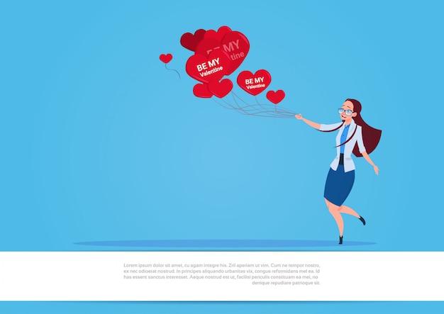 Muchacha que sostiene los globos de aire en forma de corazón rojos sobre el fondo azul concepto feliz del día de fiesta del día de san valentín