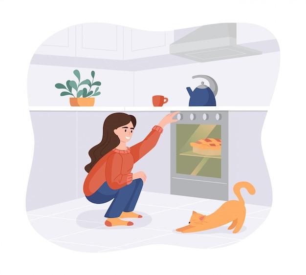 La muchacha sonriente cuece un plato en el horno. mujer con gato en la cocina preparando comidas caseras para la cena.