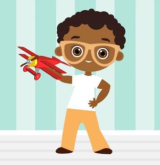 Muchacho afroamericano con gafas y avión de juguete. niño jugando con avion