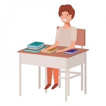 Muchacho joven del estudiante que se sienta en el escritorio de la escuela
