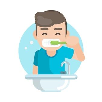 Muchacho lindo feliz que cepilla los dientes en cuarto de baño