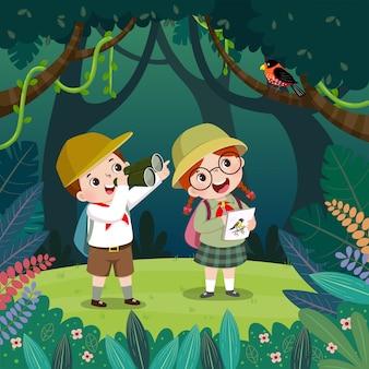 Muchacho lindo que mira el pájaro a través de los prismáticos y la muchacha que dibuja los pájaros en el bosque. los niños tienen aventura al aire libre en verano.