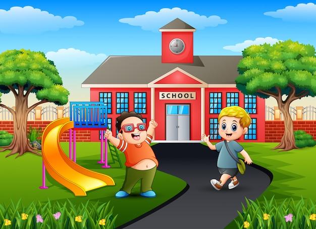 Los muchachos con mochilas frente al edificio de la escuela.