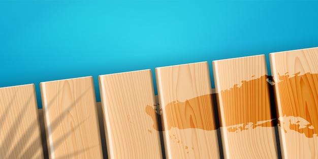 Muelle de madera con sombra de palma y mancha de agua.