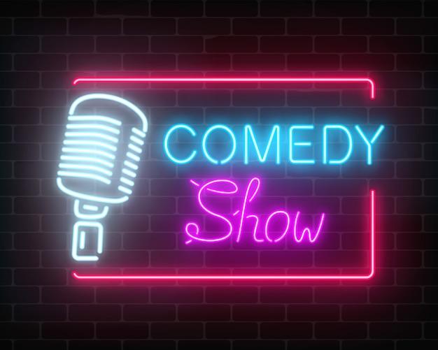Muestra de comedia de neón con micrófono retro en una pared de ladrillos