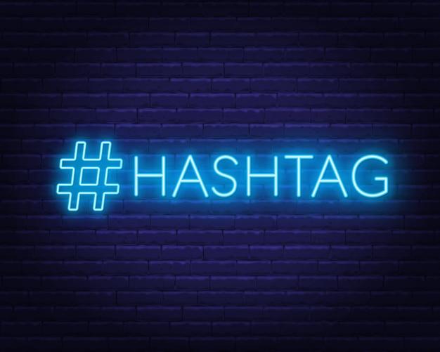 Muestra de hashtag de neón sobre fondo de pared de ladrillo.
