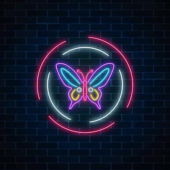 Muestra de neón que brilla intensamente batterfly púrpura en marcos redondos en fondo oscuro de la pared de ladrillo. emblema de volante de primavera en círculo.