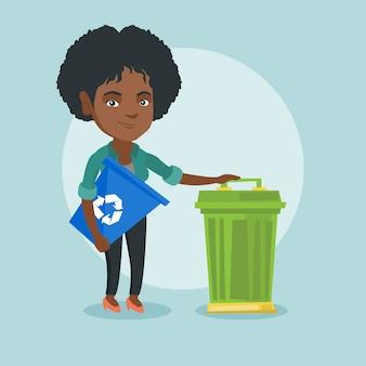 Mujer africana con papelera de reciclaje y bote de basura.