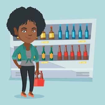Mujer africana con paquete de cerveza en el supermercado.