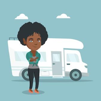 Mujer africana de pie delante de autocaravana.