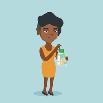 Mujer africana poniendo dólar en un frasco de vidrio.