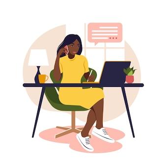 Mujer africana sentada mesa con ordenador portátil y teléfono. trabajando en una computadora. freelance, educación en línea o concepto de redes sociales. estudiar el concepto. estilo plano.