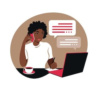 Mujer africana trabaja en una computadora portátil y habla por teléfono sentado en una mesa en casa con una taza de café y papeles.