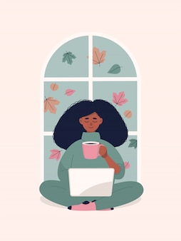 Mujer afro bebiendo café y trabajando en la computadora portátil por ventana