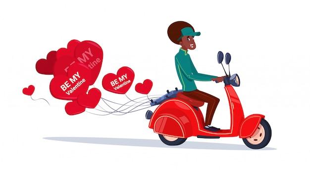 Mujer afroamericana que monta la bici de motor retra con los globos en forma de corazón concepto feliz del día de tarjetas del día de san valentín