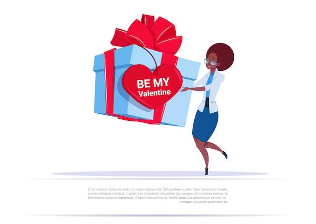 Mujer afroamericana sosteniendo una gran caja de regalo con etiqueta en forma de corazón be me valentine saludo sobre fondo de plantilla