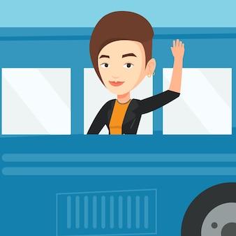 Mujer agitando la mano desde la ventana del autobús.