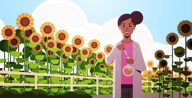 Mujer agricultor científico con tubo de ensayo haciendo experimento en girasoles investigación de campo