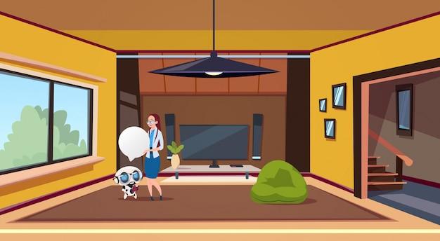 Mujer con ama de llaves robot en el interior de la sala de estar moderna