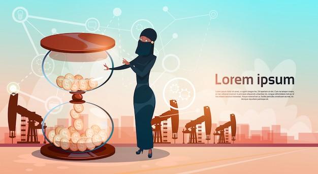 Mujer árabe con arena reloj dinero pumpjack plataforma petrolera plataforma de grúa concepto de riqueza