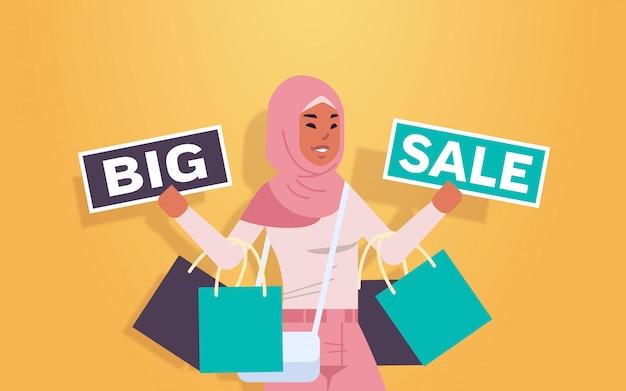 Mujer árabe con compras y pancartas de gran venta cliente de niña árabe con bolsas de compras oferta especial concepto de descuento de vacaciones retrato plano horizontal