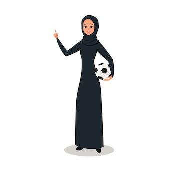 Mujer árabe con hijab sostiene un balón de fútbol.