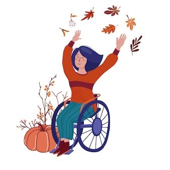 Mujer bonita en suéter, botas y jeans sentado en silla de ruedas, agitando las manos - otoño, concepto de temporada de otoño con hojas, calabaza, ramas