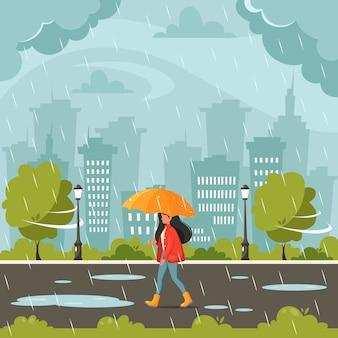 Mujer caminando bajo un paraguas durante la lluvia. lluvia de otoño. actividades al aire libre de otoño.
