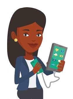Mujer cargando el teléfono inteligente de la batería portátil.