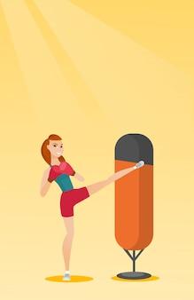 Mujer caucásica joven que ejercita con el bolso de perforación