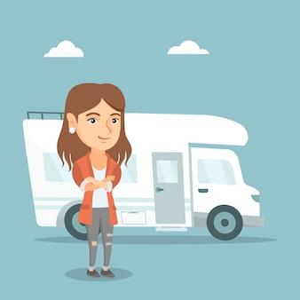 Mujer caucásica de pie delante de autocaravana.