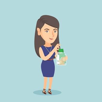 Mujer caucásica poniendo dólar en un frasco de vidrio.