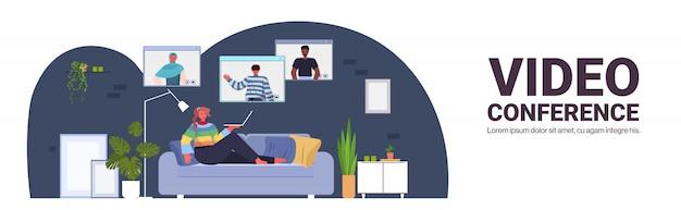 Mujer chateando con amigos de raza mixta durante la videollamada personas que tienen conferencia en línea reunión comunicación concepto sala de estar interior horizontal longitud completa copia espacio ilustración