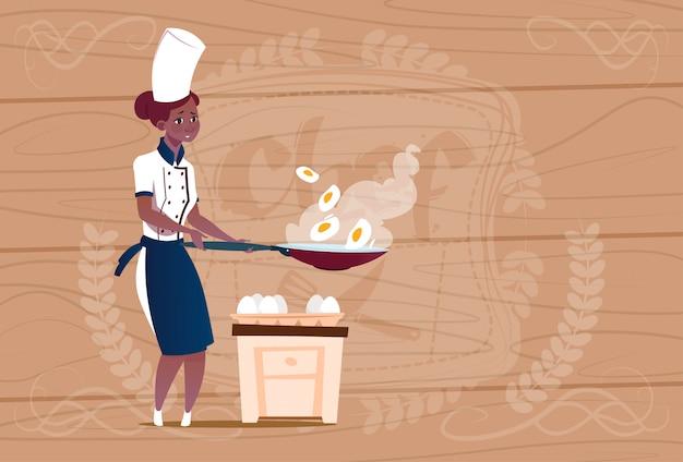 Mujer chef afroamericano cocinero cocinando huevos fritos jefe de restaurante de uniforme sobre fondo con textura de madera
